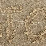 Das Wort STOP ist in den Sandgeschrieben
